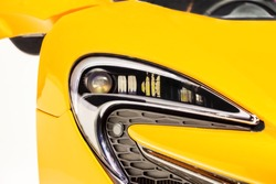 Yellow sport car headlight. Car detail. The front lights of the yellow car, in sports car. Developed Car's front light.