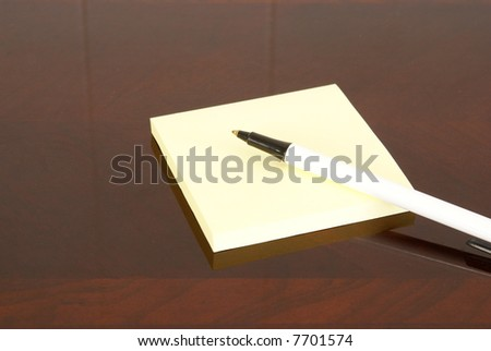 Yellow square notepad and pen on dark wood desk