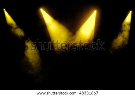 Yellow stage spotlights in smoke over black background