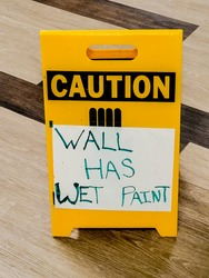 Yellow standing Caution sign sitting on parquet wood floor with white paper hand lettered Wall Has Wet Paint taped to it