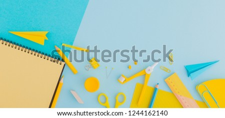Yellow stationery on a blue pastel background. Creative, school concept flat lay.