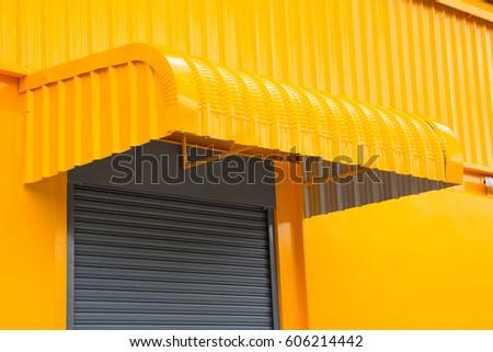 yellow steel awning over shutter metal door