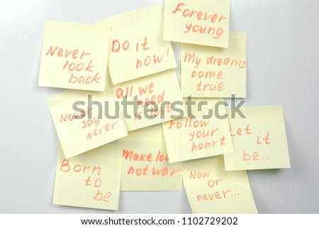 Yellow sticker paper sheets with motivation phrases on a white board. #1102729202