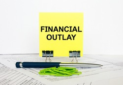 Yellow sticker with text Financial Outlay stands on office clips. Next to it is a blue pen with green paper clips. It can be used as a business and financial concept