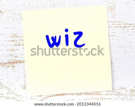 Yellow sticky note on wooden wall with handwritten inscription wiz Zdjęcia stock ©