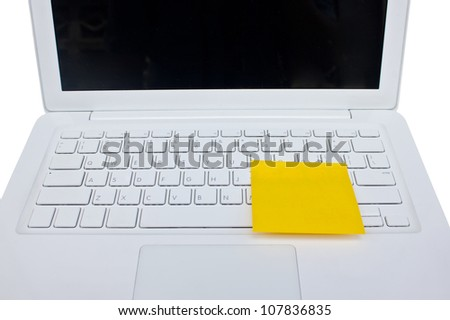 Yellow sticky note post on white laptop.