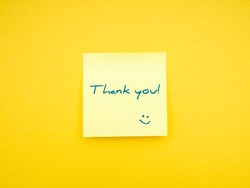 Yellow sticky note with caption Thank You! on vibrant yellow background. Studio shot photography