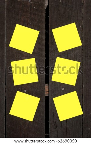 Yellow sticky notes on a wooden wall.