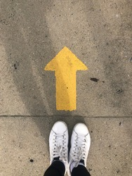 Yellow straight arrow sign and white shoes. Straight direction concept. Journey concept