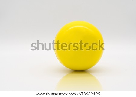 Yellow stress ball rolling on reflection floor isolated on white background. Сток-фото ©