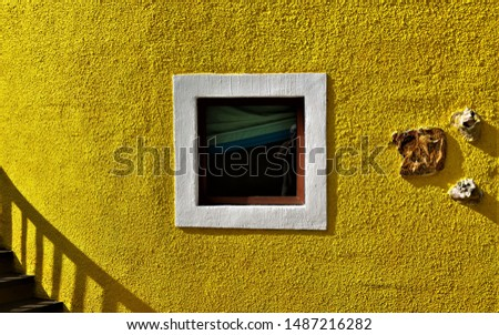 Yellow stucco wall with framed window and stairway #1487216282