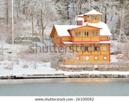 Yellow summer house with snow. The yellow color with white framing common in Sweden.