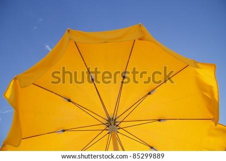 Yellow sun umbrella against blue sky