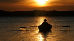 Yellow sundown over lake and silhouette of fisherman in cowboy hat on rowing boat