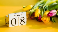 Yellow, sunny greeting card for Women's Day on March 8 with the number and month. Beautiful background of delicate tulips. March 8 and the concept of