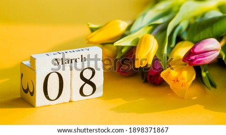"""Yellow, sunny greeting card for Women's Day on March 8 with the number and month. Beautiful background of delicate tulips. March 8 and the concept of """"Women's Day""""."""
