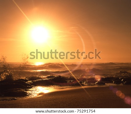 yellow sunrise over sandy beach and ocean waves