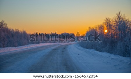 Yellow sunrise, winter road and winter forest in winter