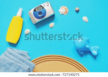 Yellow sunscreen bottle, blue terry towel, retro camera, seashells, hat and toy dolphin. Mockup, free space for text. Travel concept