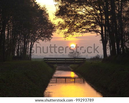 Yellow sunset over bridge and canal in a park - stock photo
