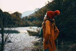 Yellow sweater red hat woman on the nature in the mountains