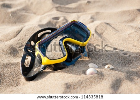 Yellow swimming mask on sea beach .face mask on the beach