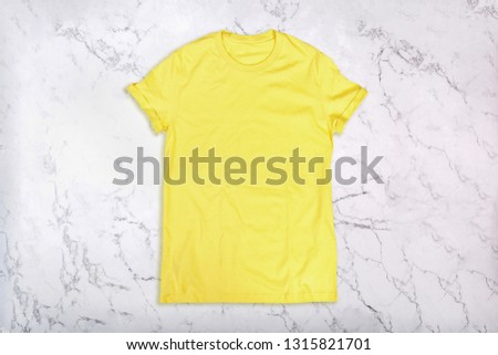 Yellow t-shirt on white marble background. Flat lay. Top view #1315821701