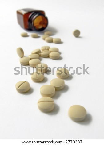 yellow tablets spilling from brown medicine bottle; differential focus