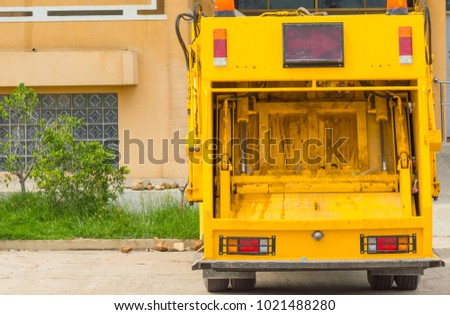 Yellow tailgate of garbage truck.A truck parking in front of building. #1021488280