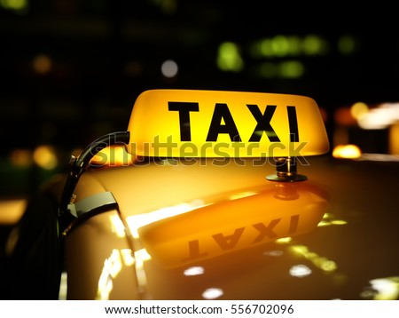 Yellow taxi sign at night. Taxi car on the street at night. Taxi car roof sign on bokeh background