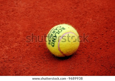 Yellow tennis ball lies on the red clay court of Roland Garros, Paris