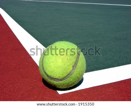 Yellow tennis ball on corner white line of red and green hard surface court - stock photo