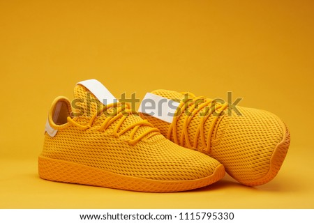 Yellow tennis modern shoes isolated on orange background ストックフォト ©