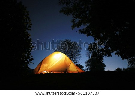 yellow tent grow in the dark blue sky
