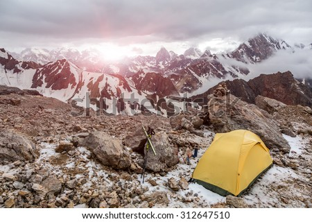 Yellow tent on mountain landscape.\ Small Alpine camping Tent located on rocky terrain stone surface and high mountain hills and peaks on background evening sun light