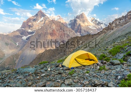 Yellow tent on mountain landscape.\ Small camping single tent located on rocky terrain stone surface and high mountain hills and peaks on background