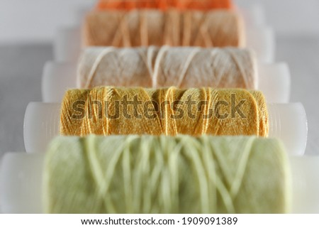 Yellow thread. Several bobins of thread in different shades of yellow, beige and light green. A set of sewing thread reels on a white background. Background with yellow spools of thread.Selective focu