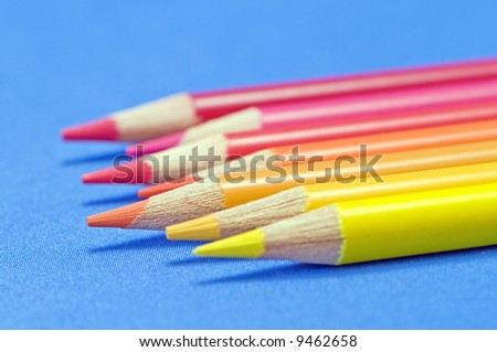 Yellow to red pencils macro on blue