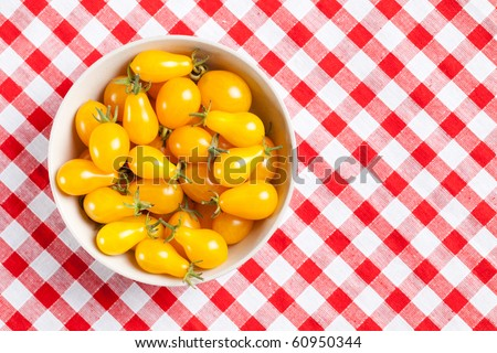 yellow tomatoes on picnic tablecloth