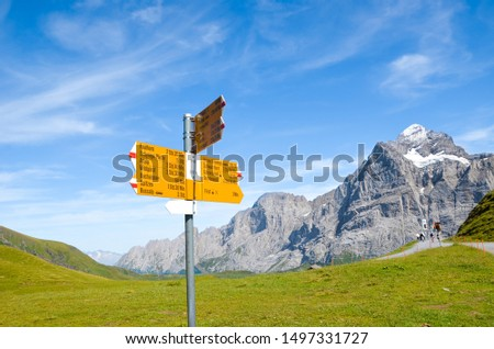 Yellow tourist sign in First, Switzerland giving distances and directions to hikers in the Swiss Alps. Popular hiking paths by Grindelwald leading to Bachalpsee. Summer Alpine landscape in background. #1497331727