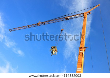 Yellow tower crane on a construction site on a sunny day with deep blue sky in the background. The construction workers already finished their work, this is why the saw is pulled up by the crane.