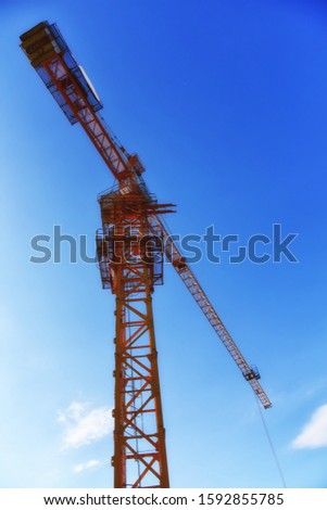 Yellow tower cranes at construction site. Construction site with tower cranes against blue sky. Crane and building construction site at sunset. Selected focus