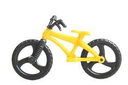 Yellow toy bike with black wheels on a white background isolated.