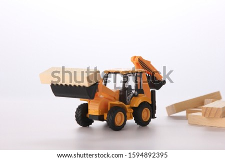Yellow toy bulldozer lifting in a bucket wooden cubes wooden cubes in the background, on a white background.