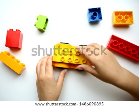 Yellow toy car in the hands of a small man. Colored blocks on white table. Children's toys are scattered on the table. #1486090895