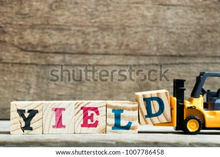 Yellow toy forklift hold letter block D to complete word yield on wood background