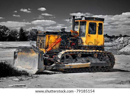 yellow track-type tractor on black and white background