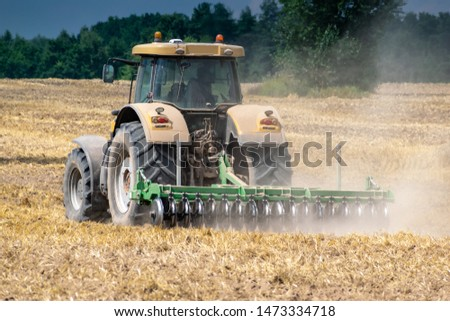 Yellow tractor cultivating the field after harvesting rear view