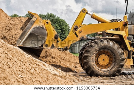 Yellow tractor loader is picking up a bucket of earth, mechanical, ladle with earth