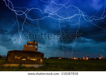Yellow tractor on dramtic sky background